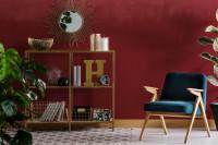 Modré retro kreslo v obývačke s bordovou stenou
