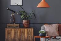 Drevená komoda a oranžová lampa v sivej obývačke