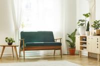Zelená pohovka a nízka drevená komoda v bielej retro obývačke