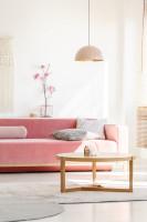 Ružová pohovka a okrúhly konferenčný stolík vo svetlej obývačke