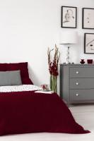 Sivá komoda a manželská posteľ s bordovými obliečkami