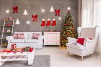 Biele kreslo ušiak a pohovka v škandinávskej obývačke s vianočnými dekoráciami