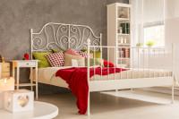 Biela kovová manželská posteľ v romantickej spálni