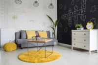 Jednoduchá obývačka s rozkladacím gaučom a a žltým kobercom