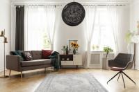 Sivá pohovka a kreslo v priestrannej retro obývačke