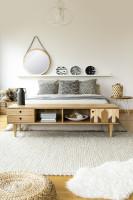 Manželská posteľ a nízka drevená komoda vo svetlej škandinávskej spálni