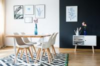 Drevený stôl a biele stoličky v čiernobielej jedálni