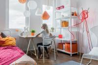 Písací stôl a kovový regál v bielej študentskej izbe s oranžovými akcentami