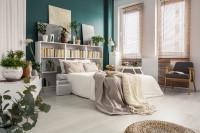 Biela posteľ v škandinávskej spálni s tyrkysovou stenou