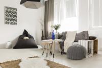 Pohovka a sada okrúhlych konferenčných stolíkov v útulnej škandinávskej obývačke