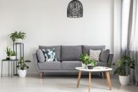 Sivá pohovka a drevený stolík s kovovými doplnkami