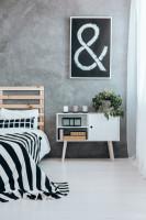 Drevená manželská posteľ a nízka biela komoda v spálni so sivou stenou
