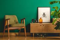 Drevená komoda a kreslo v zelenej retro obývačke