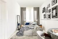 Biela posteľ v úzkej modernej spálni so zrkadlom