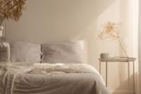 Manželská posteľ a okrúhly príručný stolík v bielych tónoch