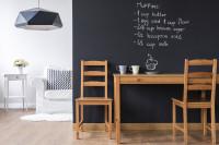 Čierna tabuľová stena v malej jedálni s dreveným nábytkom