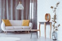 Biela pohovka so žltými dekoračnými vankúšmi a drevený odkladací stolík