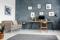 Drevený písací stôl a sivá stena so zarámovanými plagátmi