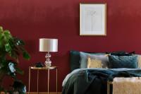 Manželská posteľ a zlatý stolík v bordovej glamour spálni