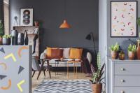 Svetlá pohovka a oranžové doplnky v sivej retro obývačke
