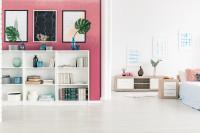 Biela knižnica v obývačke s ružovou stenou