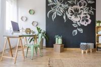 Drevený stôl s industriálnou stoličkou a čierna tabuľová stena
