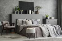 Manželská posteľ a retro kreslo v sivej spálni