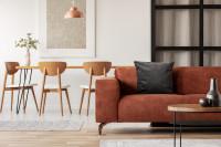 Hnedá kožená pohovka a jedálenský nábytok zo svetlého dreva