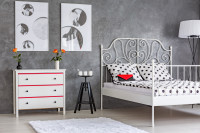 Biela kovová posteľ a komoda v sivej spálni