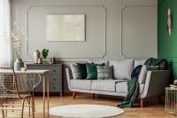 Pohovka v obývačke v sivých a zelených farbách