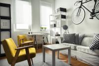 Biela látková pohovka a žlté kreslá vo svetlej škandinávskej obývačke