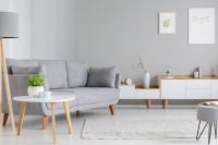 Sivá pohovka a nízke biele komody v škandinávskom štýle