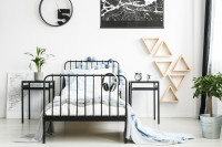 Čierna kovová posteľ a nočné stolíky v bielej izbe