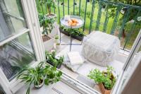 Odkladací stolík a svetlý puf na malom balkóne