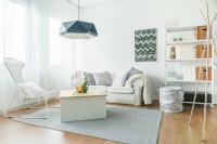 Pohodlná pohovka a kovový regál v bielej obývačke