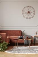 Hnedá rohová sedačka a kovový konferenčný stolík