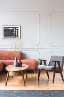 Sivé retro kreslo a drevený oválny stolík s dekoráciami