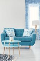 Pohovka a okrúhly stolík v obývačke v modrých tónoch