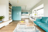 Tyrkysová pohovka a biela kuchynská linka v obývačke s kuchyňou