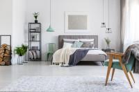 Čalúnená posteľ a čierny regál v priestrannej spálni