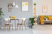 Drevený jedálenský stôl a stoličky vo svetlej obývačke so žltými dekoráciami