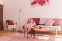 Retro pohovka s ružovými dekoračnými vankúšmi a sada okrúhlych konferenčných stolíkov