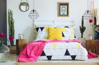 Drevená manželská posteľ v pestrej bohémskej spálni