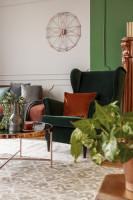 Zelené kreslo ušiak s vankúšom a okrúhly medený stolík