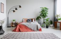 Manželská posteľ a stojanová lampa vo veľkej bohémskej spálni