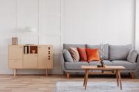 Pohovka a drevená komoda vo svetlej škandinávskej obývačke