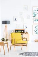 Žlté retro kreslo a drevená stojanová lampa