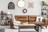 Hnedá kožená pohovka vo svetlej bohémskej obývačke
