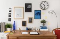 Nástenné hodiny a dekorácie nad dreveným písacím stolom
