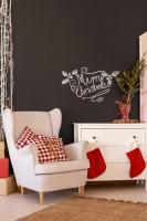 Biele kreslo a komoda v kontraste s čiernou stenou a červené vianočné dekorácie